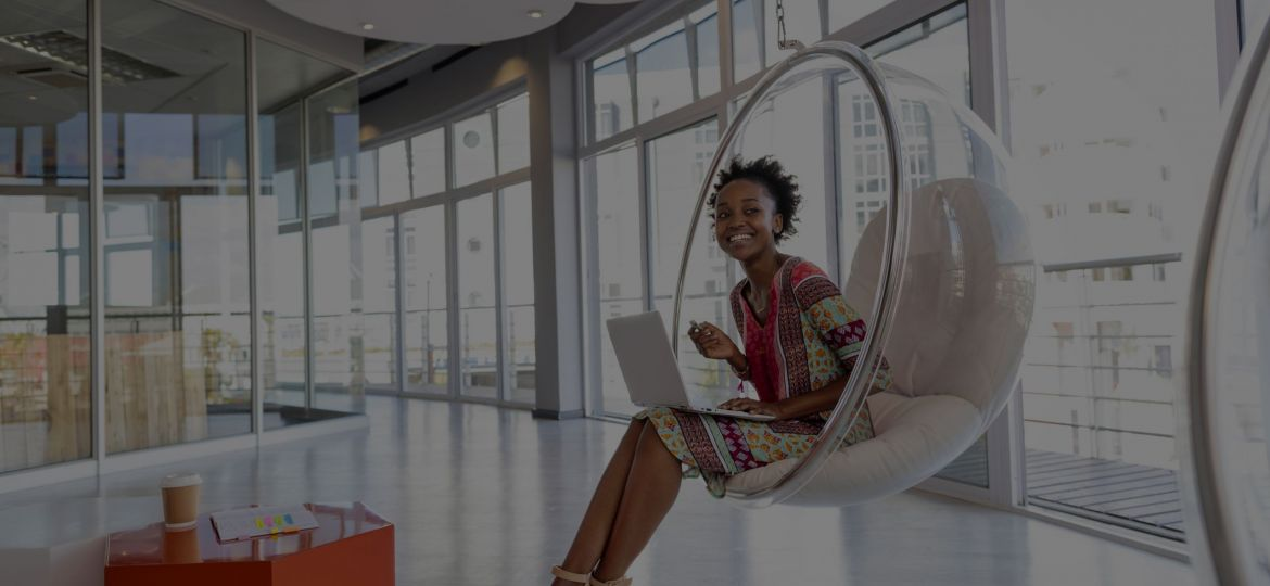 Woman using a notebook and sitting in the hallway of a modern office building